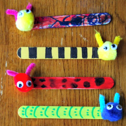 bookmark buddies made of popsicle sticks and pom poms finished with markers