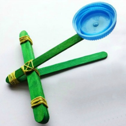 popsicle stick catapult with bottle top & rubber bands from Kids Activities Blog